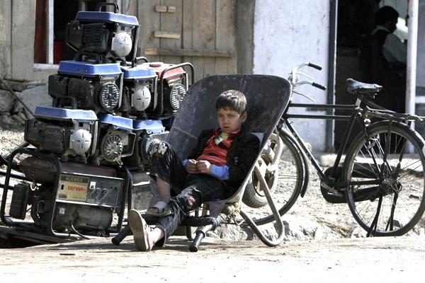 An Afghan boy waits for customer at a generator shop in Kabul, Afghanistan, on Friday, Oct. 31, 2008. (AP Photo/Rahmat Gul)