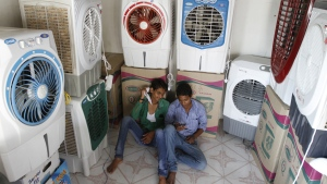 Salesboys sit in a shop selling air coolers on a hot summer day in Ahmadabad, India, Thursday, May 28, 2015. (AP / Ajit Solanki)