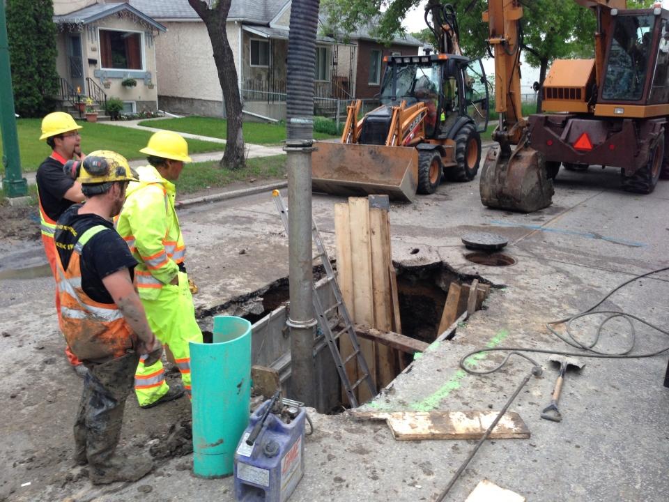 Workers examine a gaping hole on Arlington Street Thursday evening.