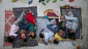 An Indian family sleeps on the roof of a house to beat the heat in New Delhi, India, Friday, May 29, 2015. In neighborhoods with irregular electric supply and sometimes to escape the heat that gets trapped in concrete houses in severely congested colonies people often sleep outside at night. (AP / Tsering Topgyal)