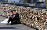 This Wednesday April 16, 2014 file photo shows a newlywed couple resting on the Pont des Arts in Paris, France. (AP Photo/Remy de la Mauviniere, File)