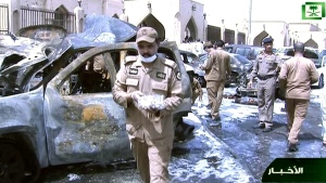 Burnt out cars are seen as investigators collect evidence, in the aftermath of a suicide bomb outside the Imam Hussein mosque in the port city of Dammam, Saudi Arabia, Friday, May 29, 2015. (Saudi Television via AP)