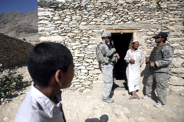 An Afghan boy looks on as U.S. soldiers speak with an Afghan man during a patrol in the Narang district of Kunar province, Afghanistan, on Friday, Oct. 31, 2008. (AP / Rafiq Maqbool)