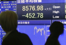 Passers-by look at an electronic stock board in downtown Tokyo Friday, Oct. 31, 2008. (AP / Koji Sasahara)