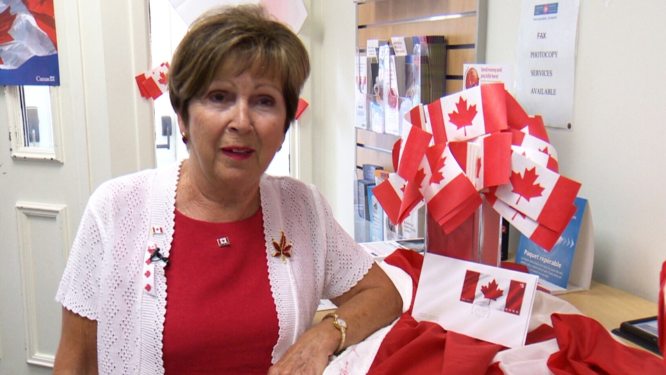 Joan O'Malley, who sewed the original Canadian flag, poses with a new stamp in St. Jacobs, Ont.