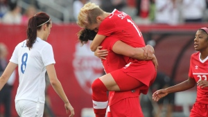 Sophie Schmidt leaps into the arms of Melissa Tancredi after scoring against England during a womens' international soccer friendly match in Hamilton, Ontario, on Friday May 29, 2015. (THE CANADIAN PRESS//Dave Chidley)