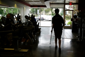 Aaron Baker, a former motocross racer who was paralyzed from the neck down in a crash in 1999, is silhouetted as he walks with his walking stick at the Center of Restorative Exercise in the Northridge section of Los Angeles on Tuesday, May 5, 2015. (AP / Jae C. Hong)