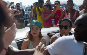 Fans surround an American classic car transporting pop artist Rihanna, wearing a green head scarf, as she leaves a building on the Malecon in Havana, Cuba on Friday, May 29, 2015. (AP / Desmond Boylan)