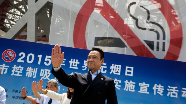 Chinese actor holds up his hand in a 'No Smoking' gesture near an anti-smoking banner displayed on the iconic Bird's Nest National Stadium on World No Tobacco Day in Beijing on Sunday, May 31, 2015. (AP / Ng Han Guan)