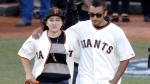 Robin Williams' children Zelda, left, and Cody, walk out to the pitcher's mound in San Francisco, on Oct. 26, 2014. (AP Photo/Charlie Riedel)