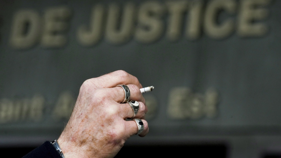 A man smokes a cigarette outside the Montreal courthouse, Monday, March 12, 2012. (Graham Hughes / THE CANADIAN PRESS)