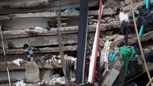 A worker toils in a collapsed garment factory building in Savar, near Dhaka, Bangladesh on April 30, 2013.  (AP / A.M.Ahad, File)
