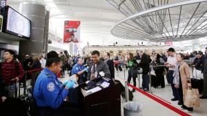 TSA officer, left, checks a passenger documents at John F. Kennedy International Airport in New York, on Oct. 30, 2014. (AP / Mark Lennihan)