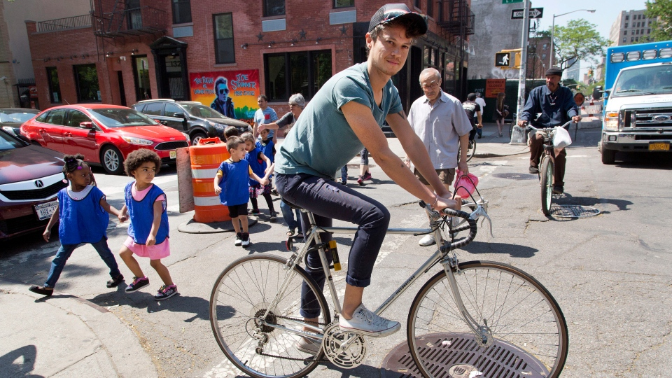 Freelance web designer Henry Brown cycles around his neighborhood in the Lower East Side of New York on May 26, 2015. Brown ditched his fledgling advertising career 11 years ago, sick of spending 15 hours a day at work and having no time for himself. (AP Photo/Mark Lennihan)