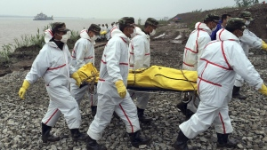Rescue workers carry a body recovered from a capsized cruise ship in the Yangtze River in Jianli county in southern China's Hubei province, Thursday, June 4, 2015. (Chinatopix Via AP)