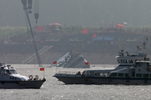 Marine boats patrol as a capsized ship is righted by cranes on the Yangtze River in Jianli county of southern China's Hubei province, as seen from across the river from Huarong county of southern China's Hunan province, Friday, June 5, 2015. The boat had been righted and teams would still try to lift the vessel even though the water inside it was weighing it down.   (AP/Andy Wong)