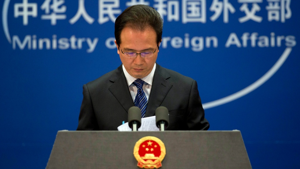Foreign ministry spokesman Hong Lei looks at the papers before he speaks during a daily briefing at the Ministry of Foreign Affairs office in Beijing, China Tuesday, May 20, 2014. (AP Photo/Andy Wong)