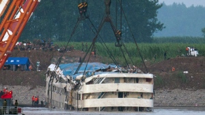 Rescuers watch the capsized ship Eastern Star being lifted by cranes on the Yangtze River in Jianli county of southern China's Hubei province, as seen from across the river from Huarong county of southern China's Hunan province, Friday, June 5, 2015. (AP/Andy Wong)
