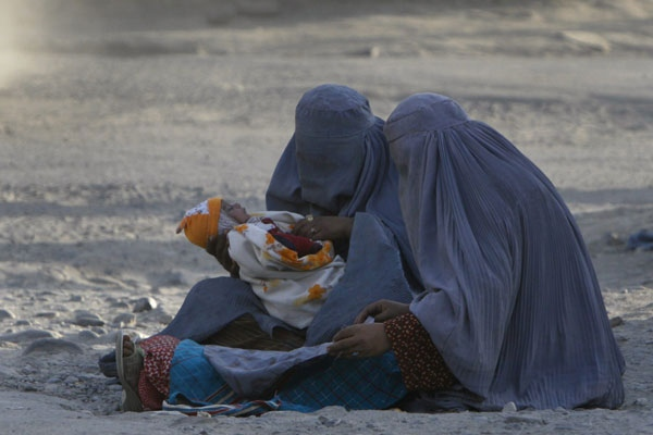 An Afghan beggar looks at the child of another on a main road during the World Food Day in the city of Kabul, Afghanistan, on Thursday, Oct. 16, 2008. (AP / Musadeq Sadeq)