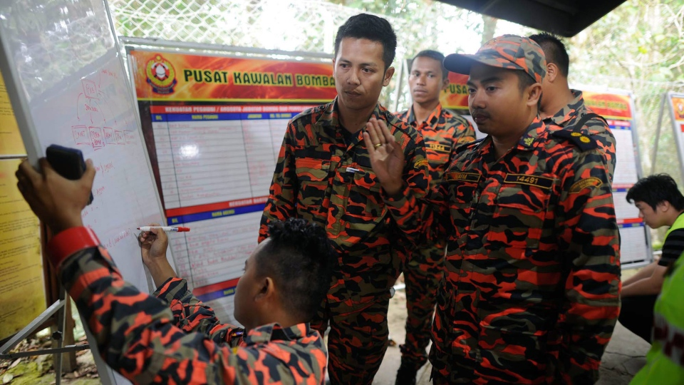 Members of the Malaysian rescue team plan as they wait for victims to be evacuated a day after an earthquake in Kundasang, a town in the district of Ranau, Malaysia, on Saturday, June 6, 2015. (Source via AP)