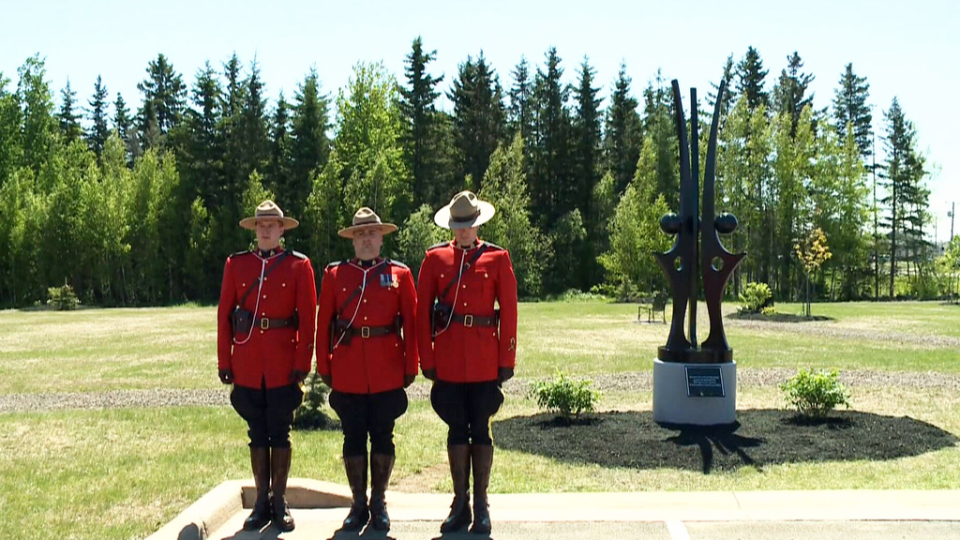 Three Mounties pose in front of a memorial honouring three RCMP constables killed during the Moncton shooting in 2014 in shown. The statue was unveiled on Sunday, June 7, 2015 in Moncton, N.B.