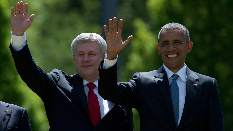 Prime Minister Stephen Harper and United States President Barack Obama wave during the G7 summit family photo at Schloss Elmau near Garmisch, Germany on Sunday, June 7, 2015. (Adrian Wyld / THE CANADIAN PRESS)