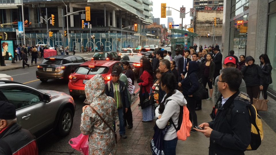 Commuters wait for a TTC bus in Toronto on Monday, June 8, 2015.