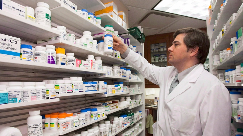 Pharmacist Denis Boissinot checks a bottle on a shelf at his pharmacy on March 8, 2012 in Quebec City.  (THE CANADIAN PRESS/ Jacques Boissinot)