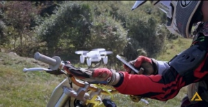 A dirt bike rider appears to use a self-flying drone to snap a dronie, a photo or video captured by a drone. (YouTube/Zano)
