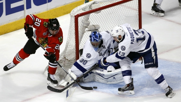 Chicago Blackhawks' Brandon Saad, left, reaches for a puck as Tampa Bay Lightning goalie Ben Bishop and Cedric Paquette, right, defend during the third period in Game 3 of the NHL hockey Stanley Cup Final in Chicago on June 8, 2015. (AP / Charles Rex Arbogast)