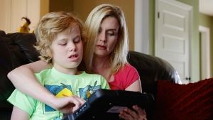 Colleen Jankovich works with her 11-year-old autistic son, Matthew, who is non-verbal and requires 24/7 care, in Omaha, Neb. on May 23, 2014.  (AP /Nati Harnik)