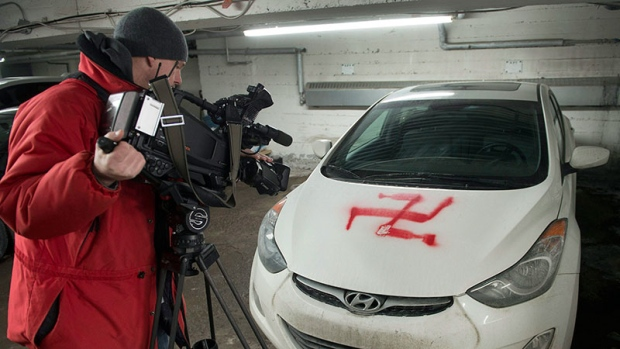 Swastika painted on one of several cars