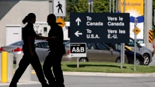 Canadian border guards are silhouetted as they replace each other at an inspection booth at the Douglas border crossing on the Canada-USA border in Surrey, B.C., on August 20, 2009. (Darryl Dyck / The Canadian Press)