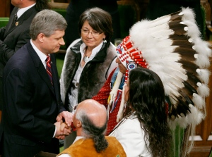 Assembly of First Nations Chief Phil Fontaine (headdress) shakes hands with Canadian Prime Minister Stephen Harper, as Inuit Tapiriit Kanatami President Mary Simon watches, after the government's official apology for more than a century of abuse and cultural loss involving Indian residential schools at a ceremony in the House of Commons on Parliament Hill in Ottawa, Wednesday, June 11, 2008. (THE CANADIAN PRESS/ Fred Chartrand)