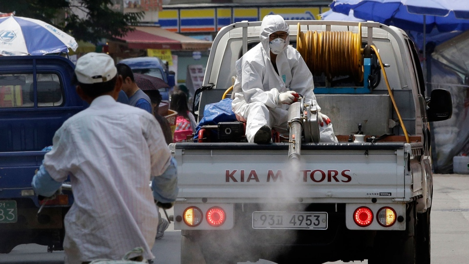 A worker wearing protective gears sitting on a truck sprays antiseptic solution as a precaution against the spread of Middle East Respiratory Syndrome (MERS) at a local market in Seoul, South Korea, Friday, June 12, 2015. (AP / Lee Jin-man)