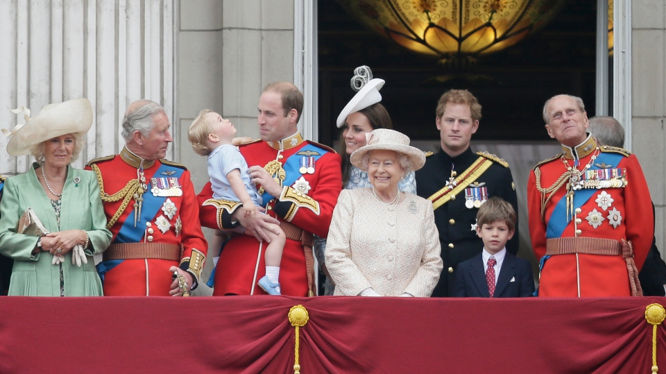 Prince William holds his son Prince George, with Queen Elizabeth II, with, left to right, The Duchess of Cornwall, The Prince of Wales, Kate, Duchess of Cambridge, Prince Harry, back, and Prince Philip, right, during the 'Trooping The Colour' parade at Buckingham Palace, in London, Saturday, June 13, 2015. (AP / Tim Ireland)