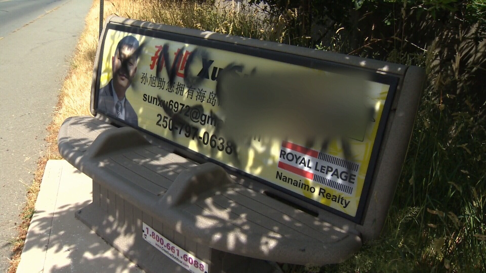 A racist epitaph is seen spray-painted on an advertisement for a Nanaimo, B.C. realtor who is Chinese. June 15, 2015. (CTV Vancouver Island)