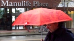A pedestrian walks past the Manulife building in downtown Vancouver, on May 3, 2012. THE CANADIAN PRESS/Jonathan Hayward