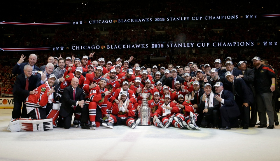 Members of the Chicago Blackhawks pose for pictures as they celebrate after defeating the Tampa Bay Lightning in Game 6 of the NHL hockey Stanley Cup Final series on Monday, June 15, 2015, in Chicago. (AP / Nam Y. Huh)