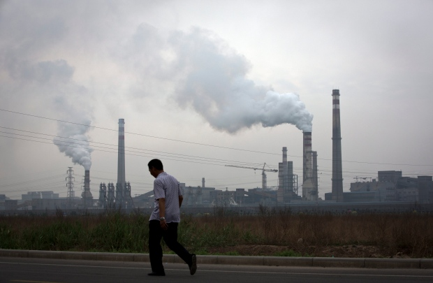 In this May 29, 2015 photo, a man walks past a coal-powered steel plant in Tianjin, China. (AP Photo/Andy Wong)