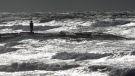 Rich Banks stands along a jetty in Galveston, Texas, photgraphing waves in the Gulf of Mexico, on June 15, 2015. (Cody Duty / Houston Chronicle)