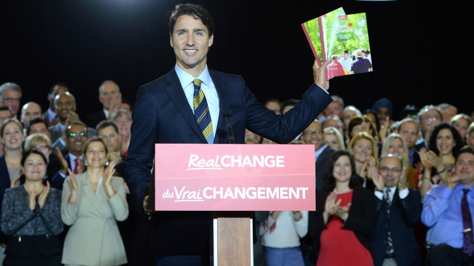 Liberal Party Leader Justin Trudeau holds up a party brochure at an announcement on fair and open government in Ottawa on Tuesday, June 16, 2015. (Sean Kilpatrick / THE CANADIAN PRESS)