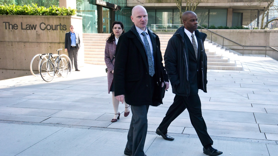 RCMP Const. Kwesi Millington, right, leaves court during a lunch break at his perjury trial in Vancouver, B.C., on Monday March 10, 2014.(Darryl Dyck / THE CANADIAN PRESS)