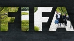 Two persons are reflected in the FIFA logo at the FIFA headquarters in Zurich, Switzerland on May 27, 2015. (AP / Michael Probst)