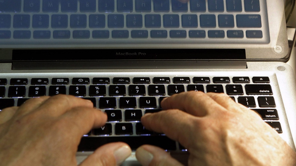 Hands type on a computer keyboard in Los Angeles, on Feb. 27, 2013. (AP Photo/Damian Dovarganes)