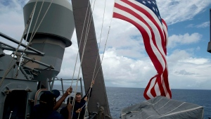 In this file photo, U.S. Navy personnel raise their national flag during a bilateral maritime exercise between the Philippine Navy and U.S. Navy, aboard the USS John S. McCain in the South China Sea near waters claimed by Beijing, June 28, 2014. (Noel Celis / AP)