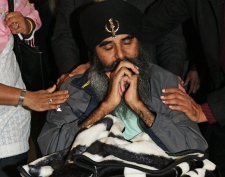 Paralyzed refugee claimant Laibar Singh pauses as supporters greet him after arriving to catch a flight to India at Vancouver International Airport in Richmond, B.C., on Monday, November 3, 2008.(Darryl Dyck / THE CANADIAN PRESS)
