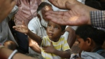 An Indian child stretchers his arm to receive free food being distributed outside a Hindu temple, in New Delhi, India on June 23, 2015. (AP / Manish Swarup)