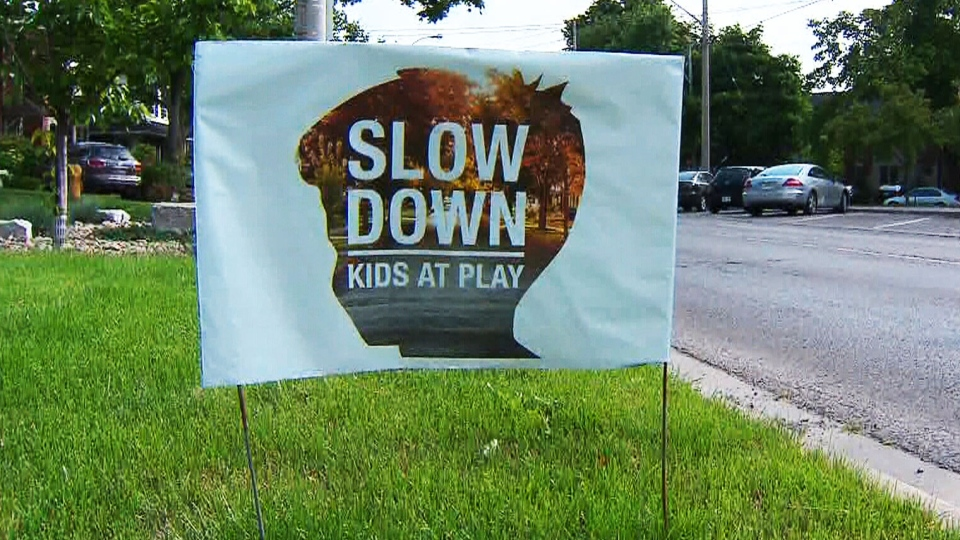 A lawn sign urges motorists to slow down on residential streets.