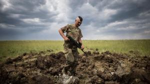 A Ukrainian serviceman investigates a crater left by a Grad rocket in the village of Toshkivka, Luhansk region, eastern Ukraine on Monday, June 15, 2015. (Evgeniy Maloletka/AP)